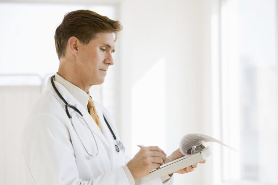 Free stock photo Doctor writing a patient report in the hospital