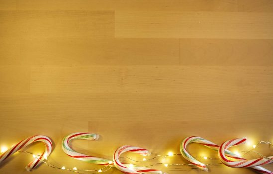 Free stock photo High angle view of candy canes and Christmas lights on wooden table