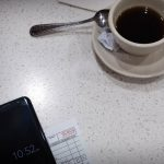 Free stock photo High angle view of coffee cup with mobile phone and receipt on table