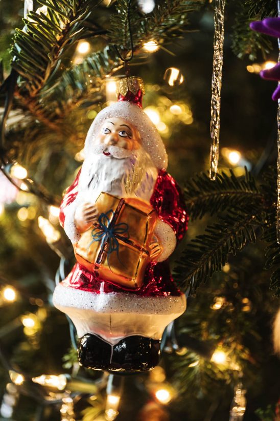 Free stock photo Close-up of Santa Claus ornament holding gift on Christmas tree