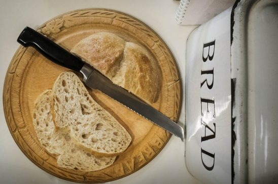 Free stock photo Overhead view of bread and knife on wooden cutting board