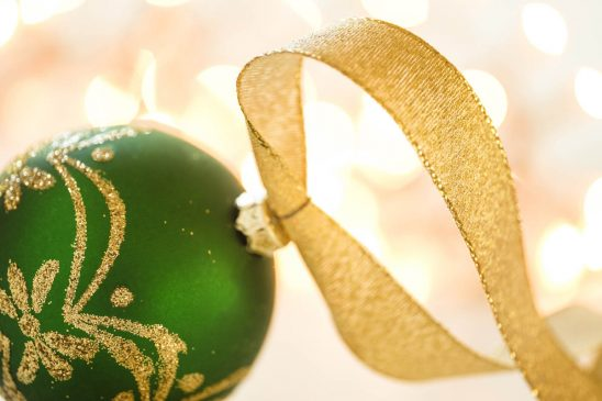 Free stock photo Close-up of green Christmas bauble with gold colored string