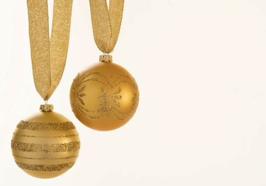 Free stock photo Close-up of gold colored Christmas baubles over white background