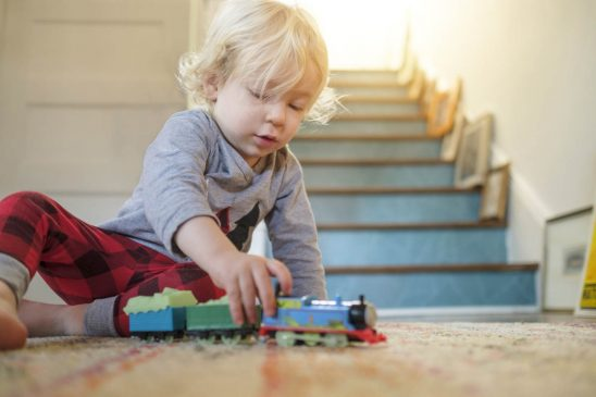 Free stock photo Cute boy playing with train toy at home