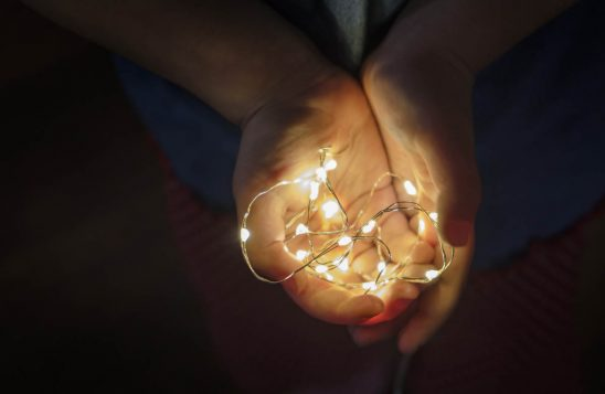 Free stock photo Child's hands holding strand of lights