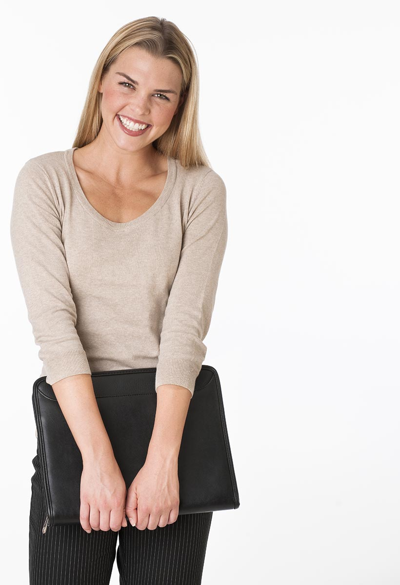 Free stock photo A young woman is holding onto a notebook and looking at the camera