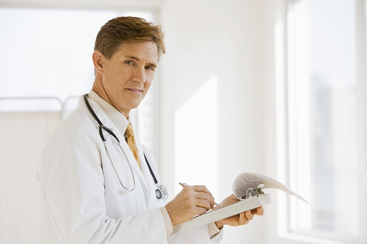 Free stock photo Doctor writing a report and looking at camera