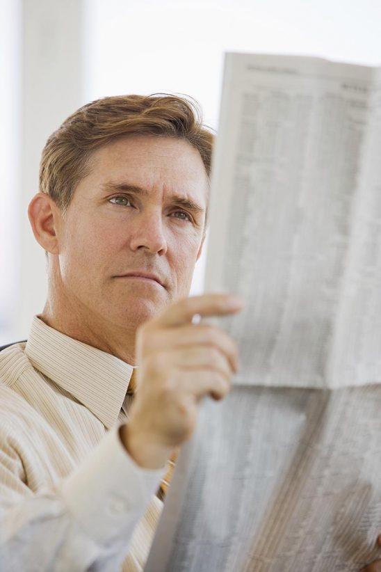 Free stock photo Business executive reading financial newspaper