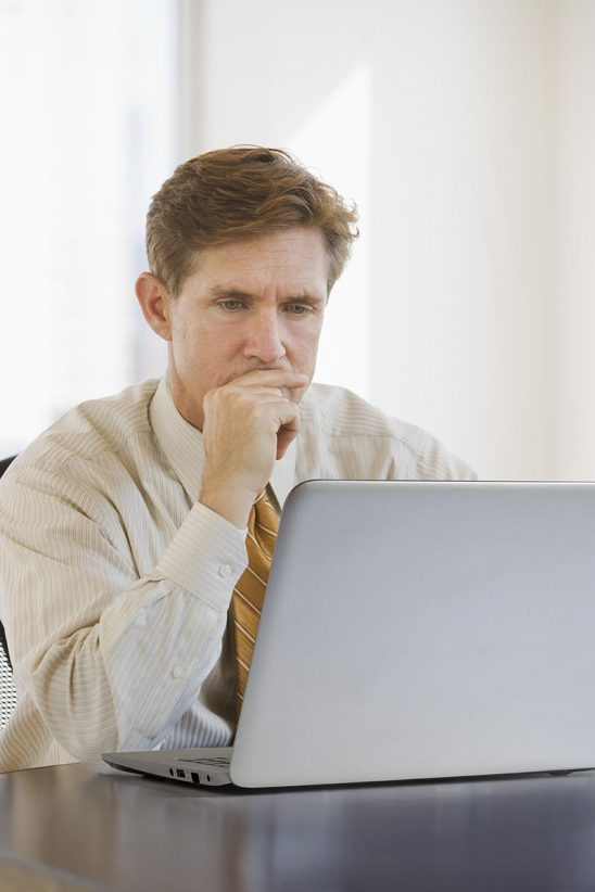 Free stock photo Business executive looking at a laptop in his office
