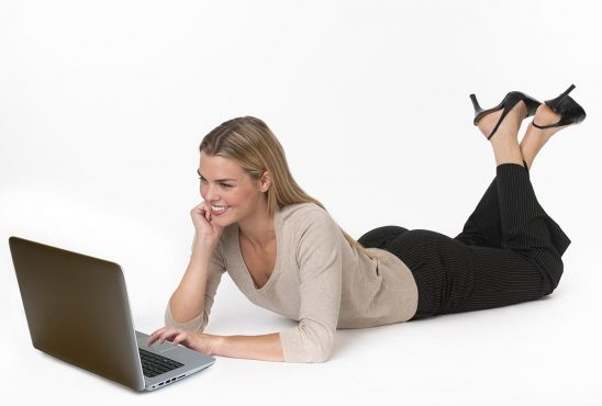 Free stock photo A young woman lying on the floor and working on a laptop