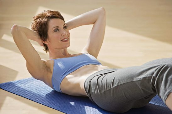 Free stock photo Smiling woman doing situps on an exercise mat