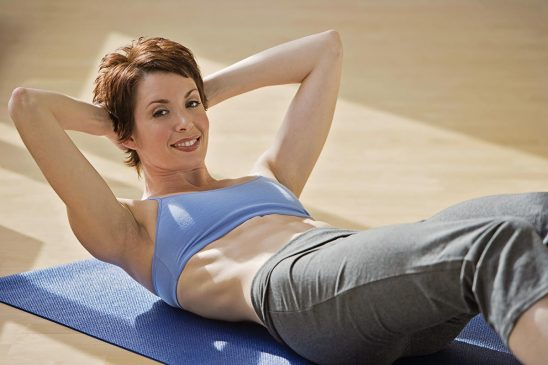Free stock photo Woman doing situps and smiling at the camera