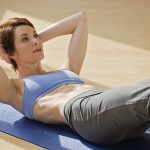 Free stock photo Woman doing situps on an exercise mat