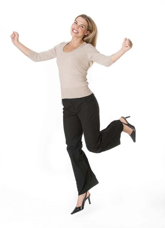 Free stock photo Young blond woman jumping against a white background and smiling at the camera