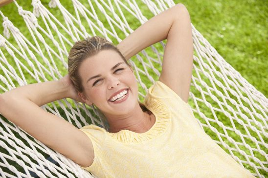 Free stock photo An attractive young woman relaxing outside in a hammock and smiling
