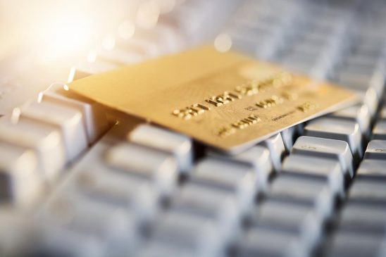 Free stock photo Gold credit card resting on a computer keyboard