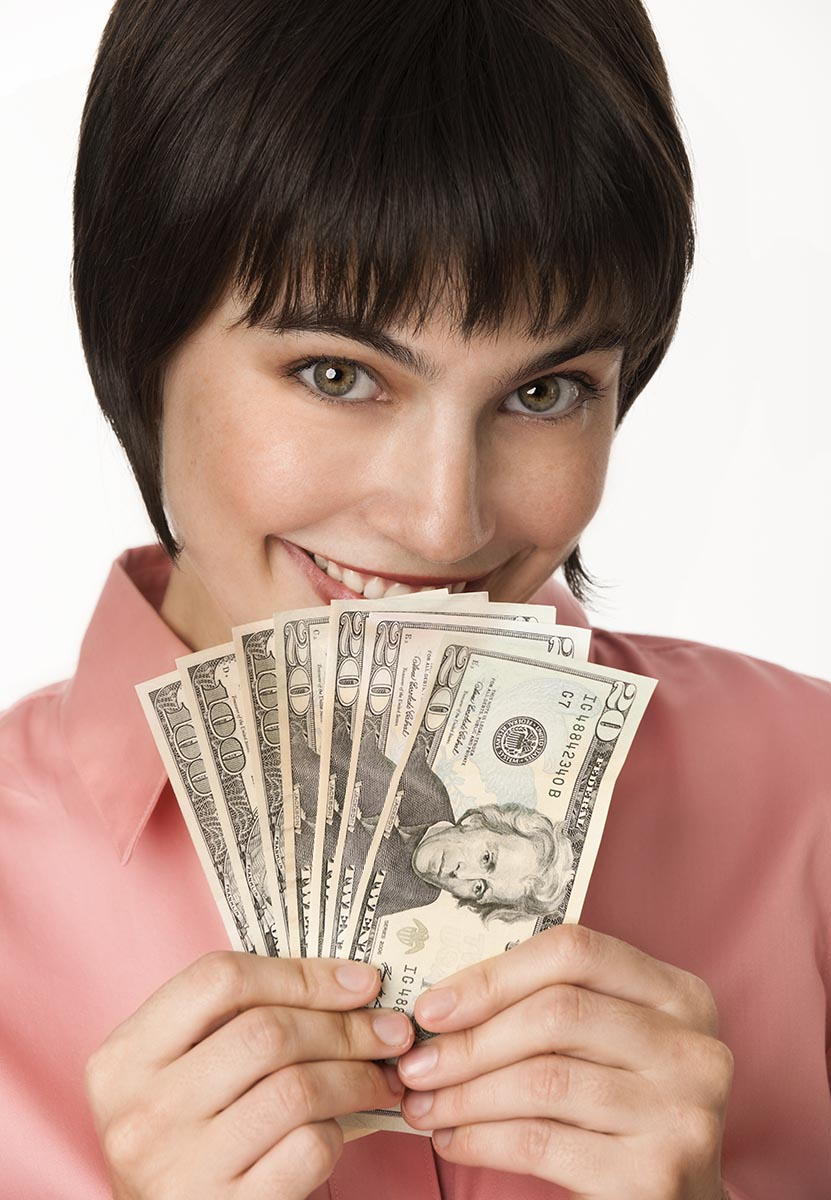 Free stock photo A beautiful brunette woman holding a fanned-out stack of cash and smiling