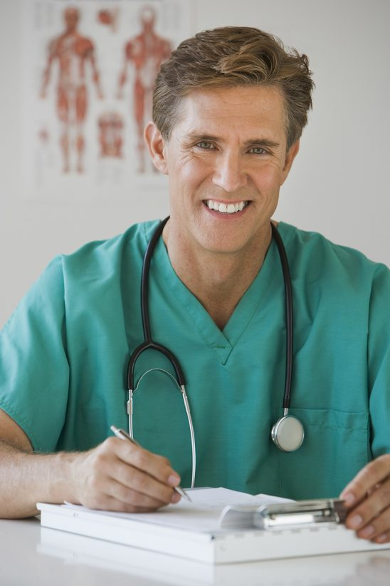 Free stock photo Doctor filling out a report at his desk