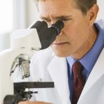Free stock photo Medical professional looking through a microscope
