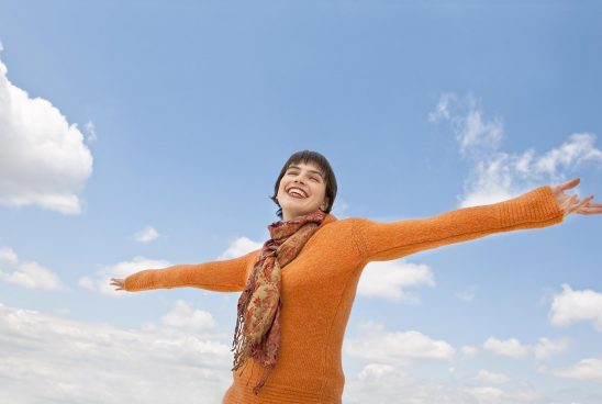 Free stock photo A smiling young woman standing with outstretched arms against the sky.