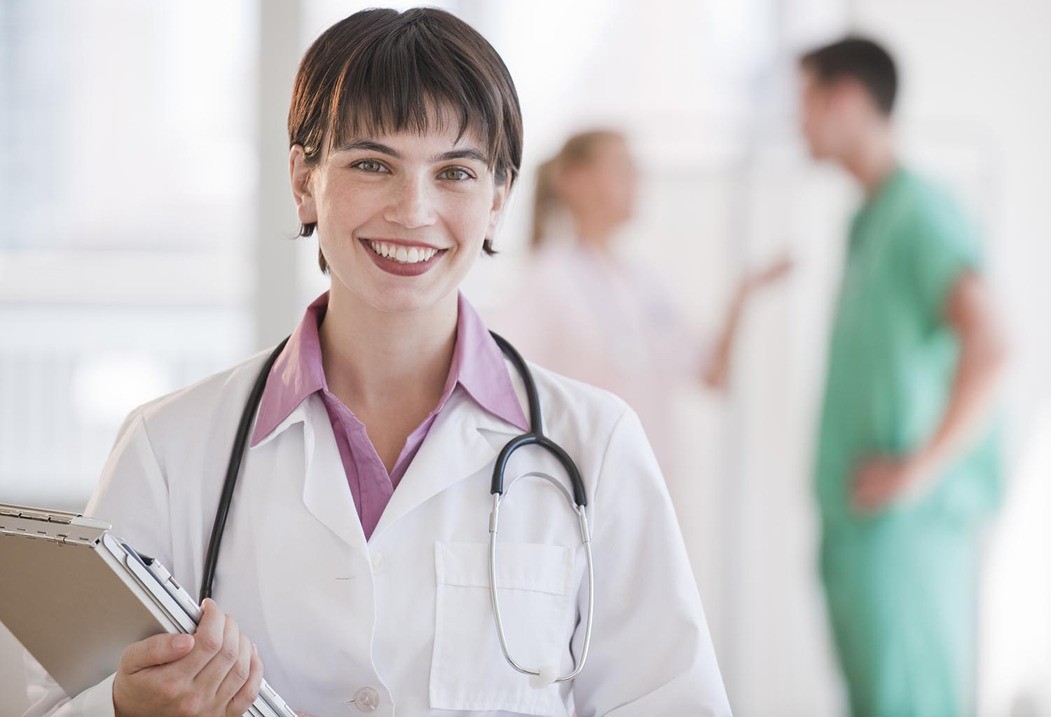 Free stock photo A young female medical professional is smiling at the camera.