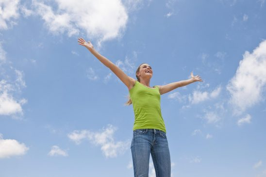Free stock photo A smiling young woman is standing outside against the sky with outstretched arms against the sky.