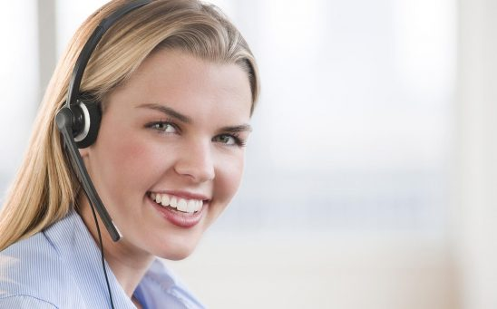 Free stock photo Portrait of a young woman service representative smiling with a headset on.