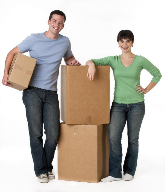 Free stock photo A couple is standing next to moving boxes and they are smiling at the camera.