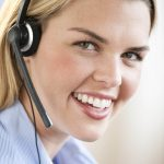 Free stock photo A young woman wearing a headset is smiling at the camera.