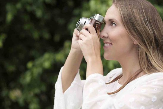 Free stock photo Close-up of smiling woman using vintage camera