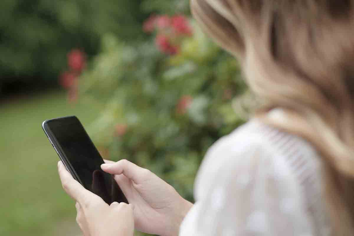 Free stock photo Close-up of woman using smart phone in park