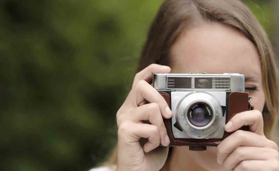 Free stock photo Close-up of woman using vintage camera