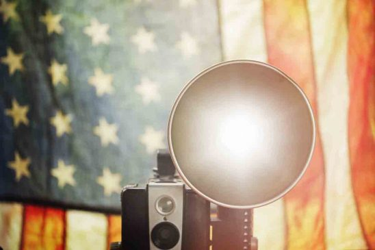 Free stock photo Close-up of vintage camera with flash against american flag