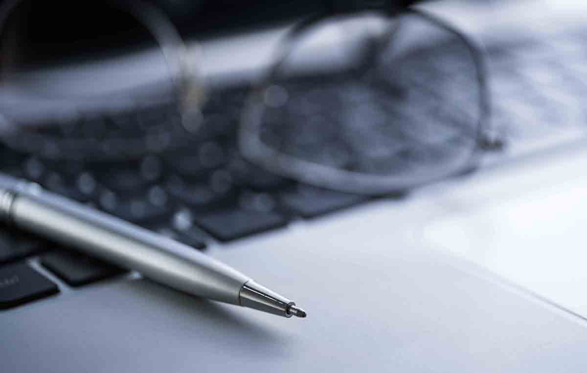 Free stock photo Close-up of pen and eyeglasses on laptop