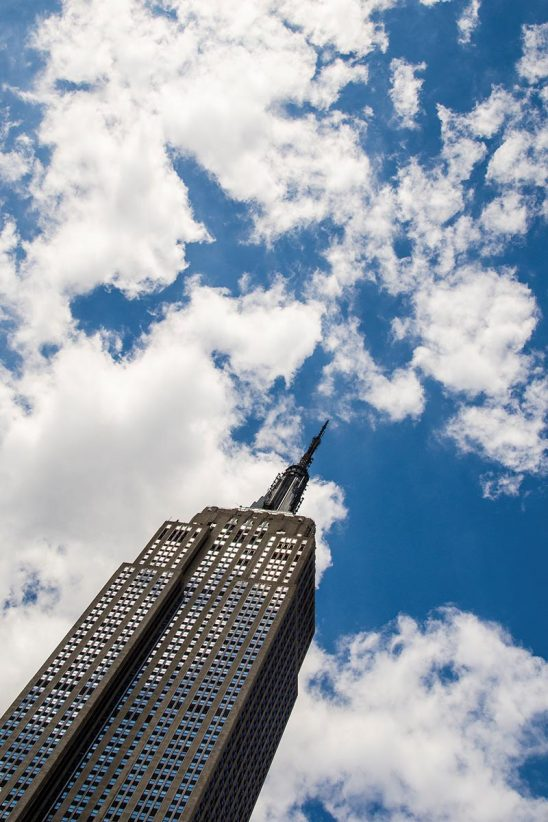 Free stock photo Low angle view of the Empire State Building against a sky with clouds
