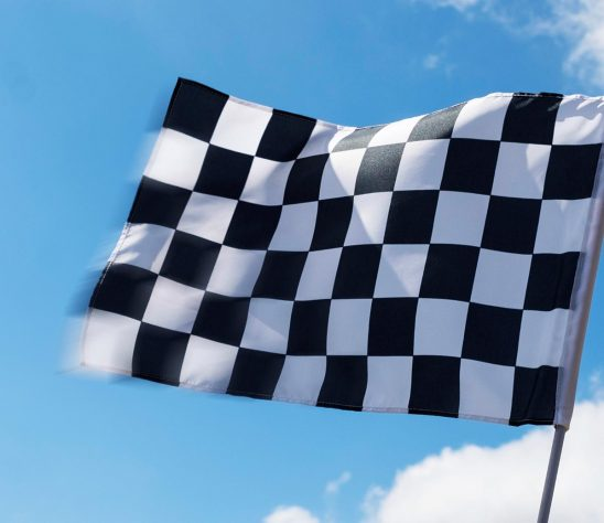 Free stock photo Checkered flag waving against the sky