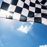 Free stock photo Checkered flag against the sun and sky