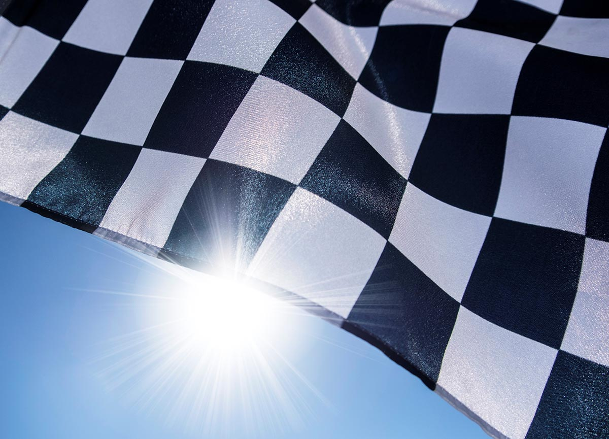 Free stock photo Waving checkered flag and sun flare