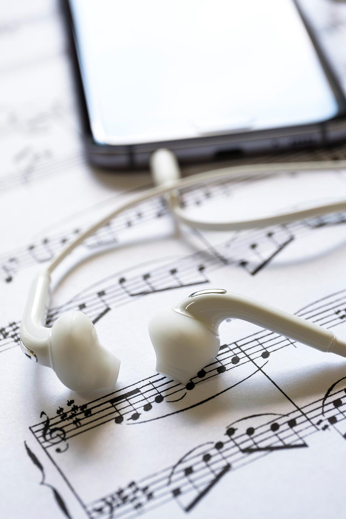 Free stock photo Earbuds and cell phone on a sheet of music