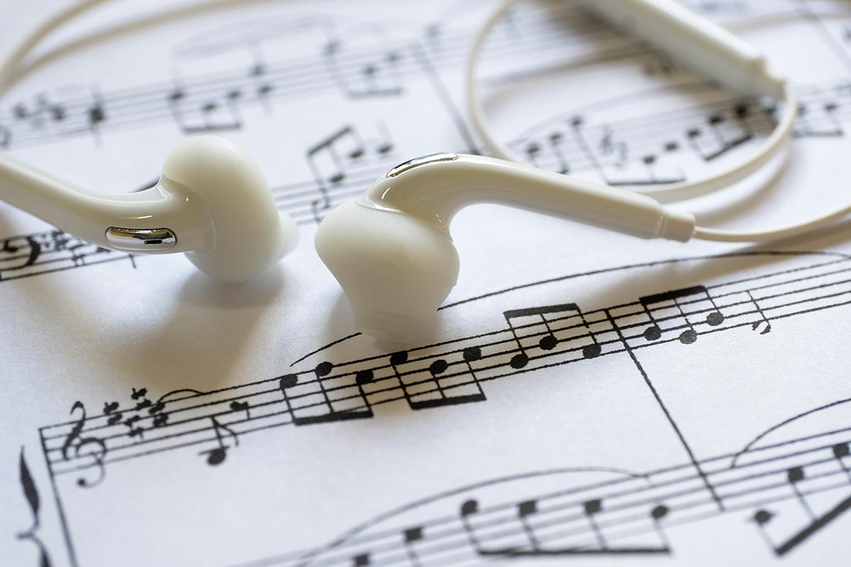 Free stock photo Close up of a pair of ear buds on a sheet of music