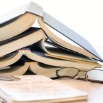 Free stock photo Stack of open books with notebook and glasses