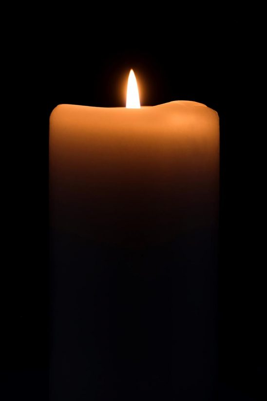 Free stock photo Tall candle lit against a black background