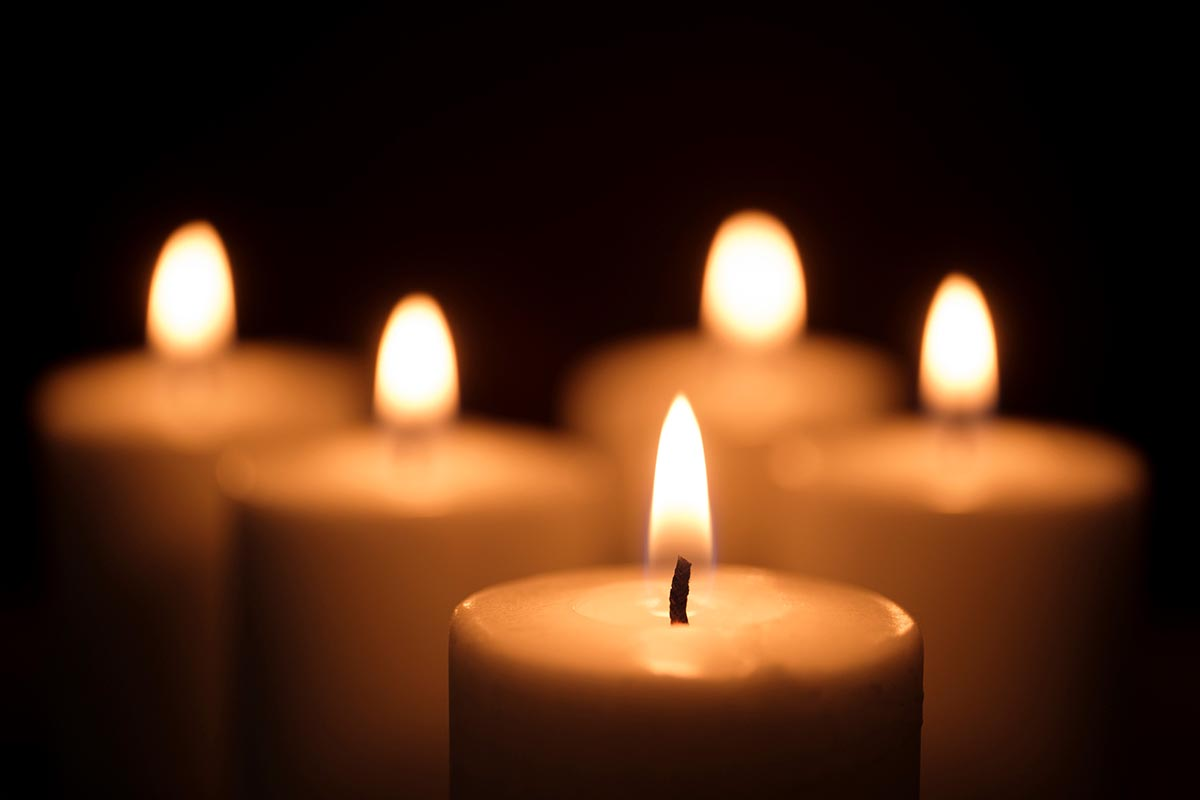 Free stock photo Group of lit candles agains a black background