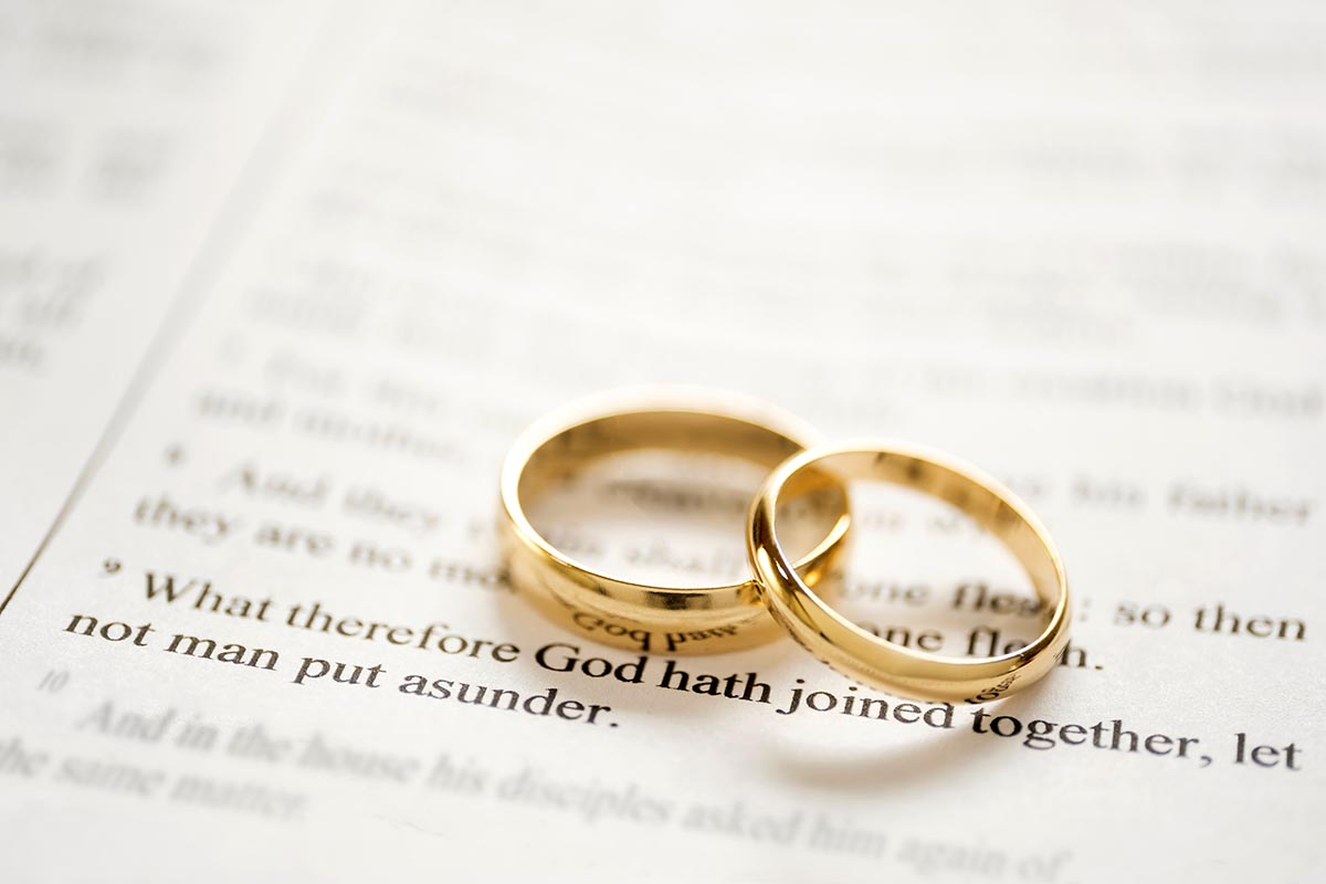 Free stock photo Two gold wedding bands resting on a Bible passage