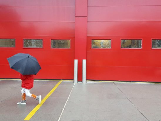 Free stock photo Child in a red coat and umbrella walking past red garage doors
