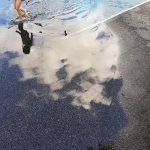 Free stock photo Little girl playing in a puddle in a parking lot