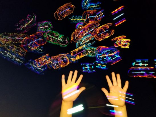 Free stock photo Childs hands playing with colorful light blurs
