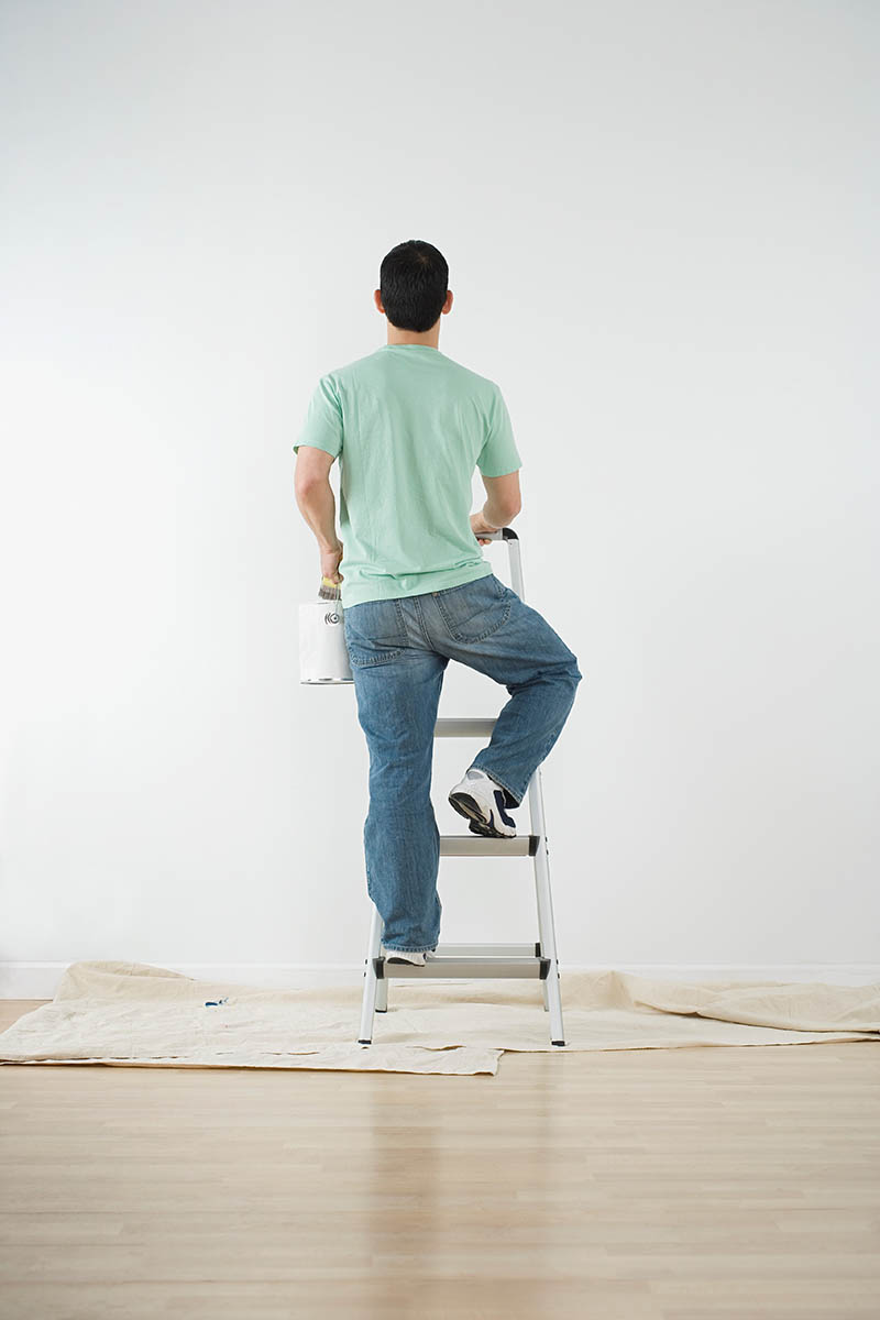 Free stock photo Man climbing a ladder with paint can to paint a wall