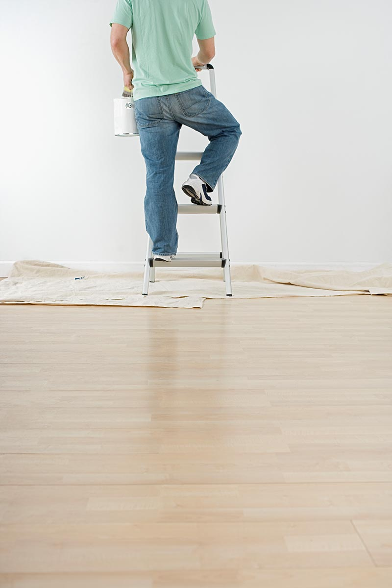 Free stock photo Partial view of a man climbing a ladder with a can of paint