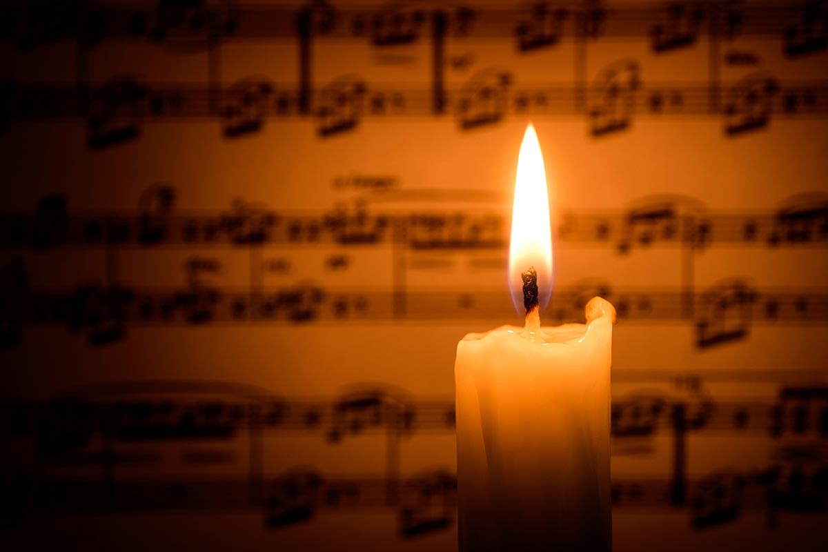 Free stock photo Candle flame light up a sheet of music